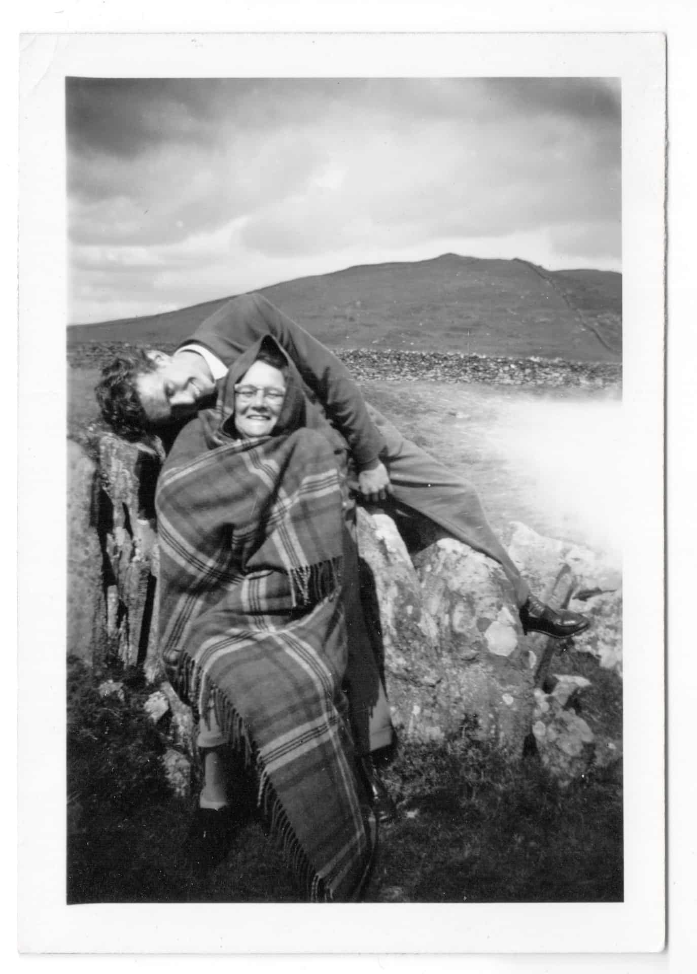 """This is Bill playing around affectionately with nan, his mom Violet. Nan and grandad always had a tartan rug in the """"motor"""". It was a Morris traveller van and the rugs came out to keep us warm whilst driving or when we were out in cold weather and then it doubled up as a picnic rug. This photograph was taken in Wales probably in the early 1960's on one of the many holidays they had there."""