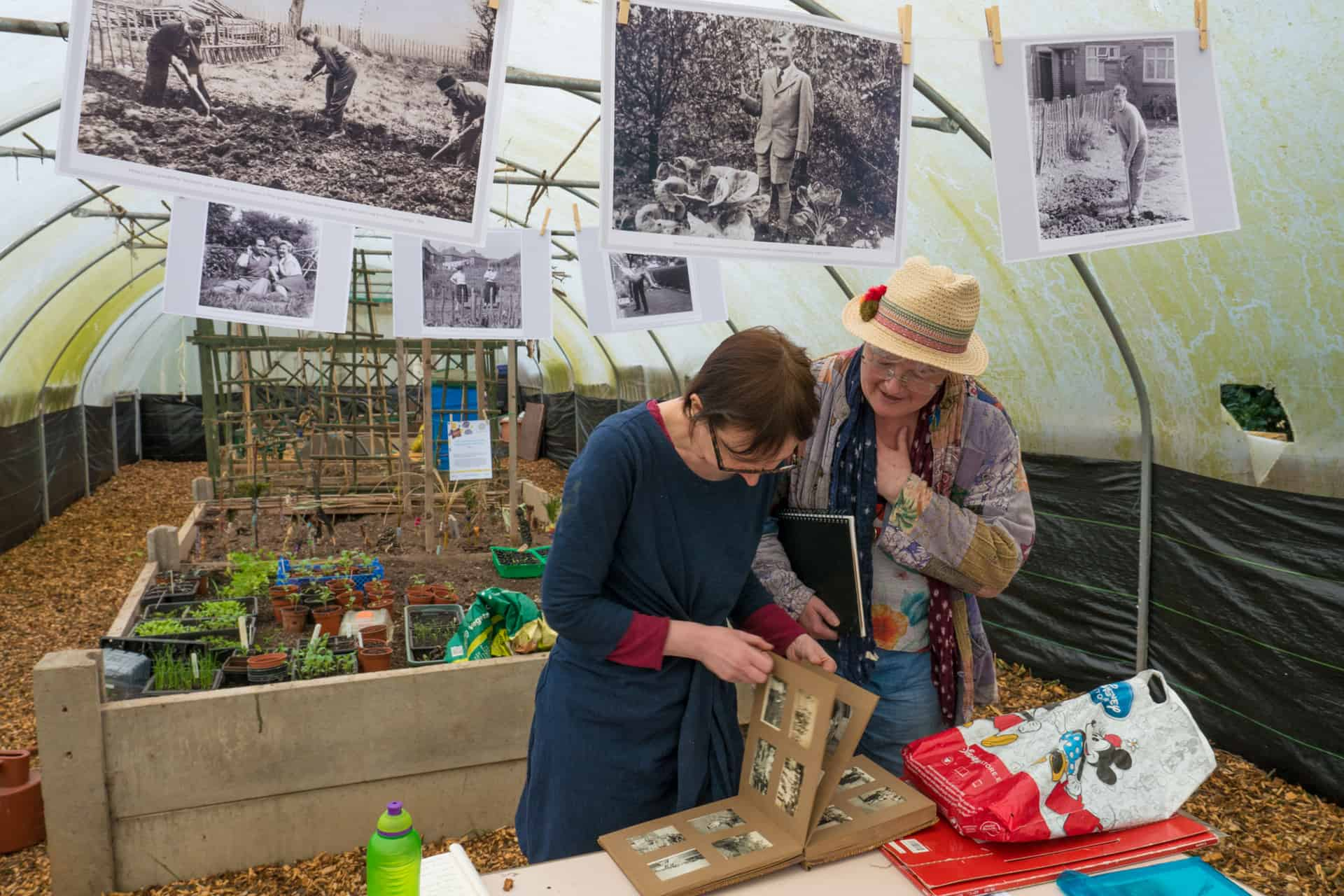 Moya Lloyd and Clare Wasserman look through a photography collection lent to the Living Memory project.