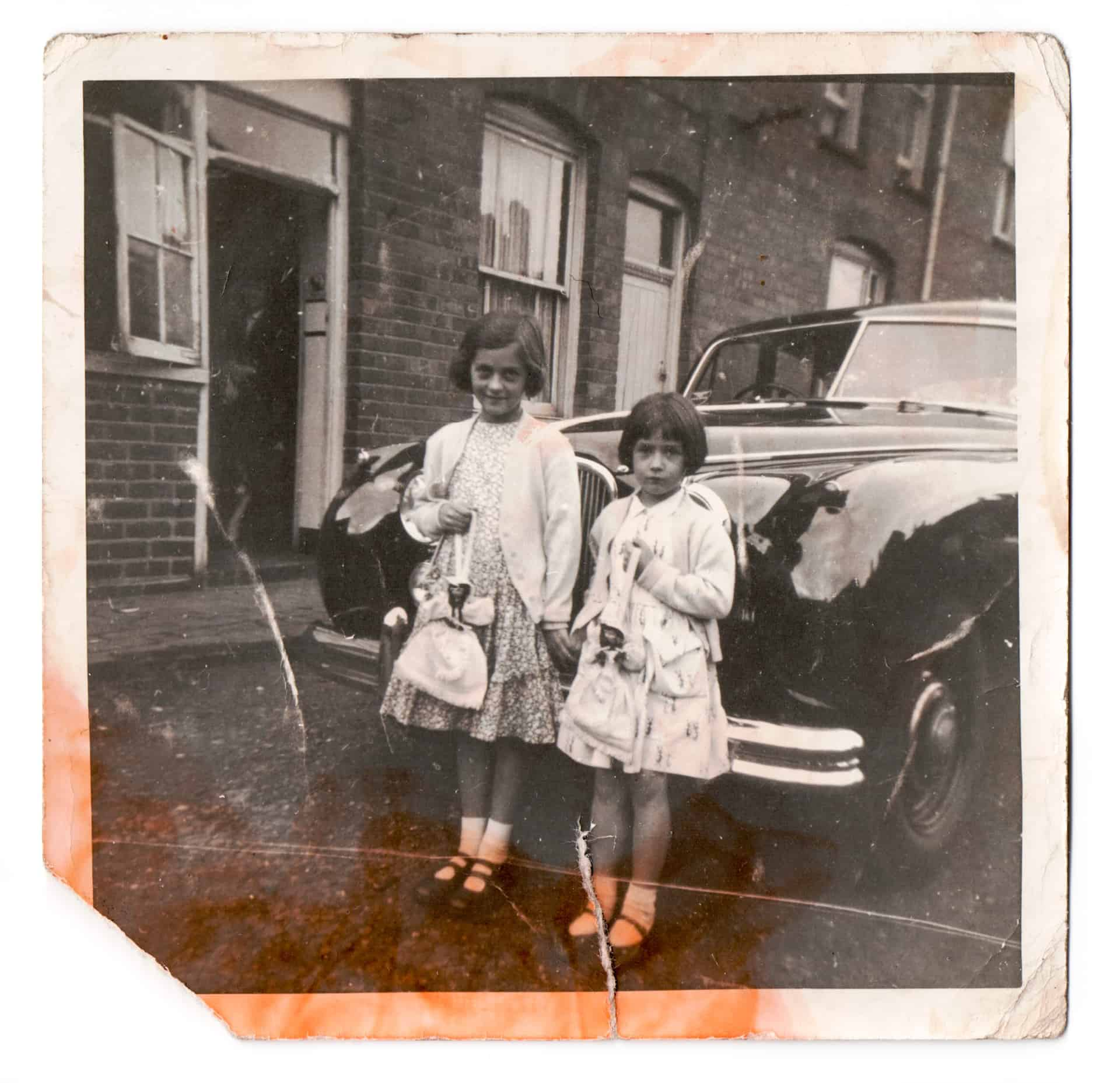 This is my sister and myself, I'm on the left. My sister's name is Denise, and she is still local -  she lives in Smethwick now. We meet all the time. In this picture we are holding what was called 'Doll Bags' They were just a little bag behind the skirt with a zip. This would be a Sunday and this would be our Sunday 'walking out' outfit at that time.