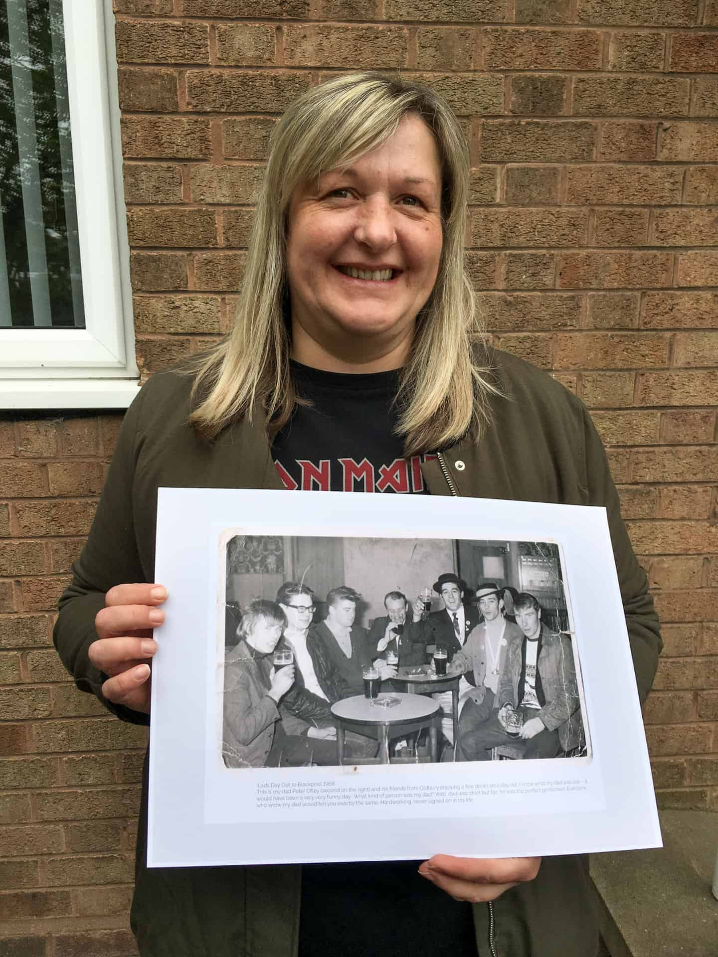 Sharon Ofley with a photo of her father and his friends from 1968