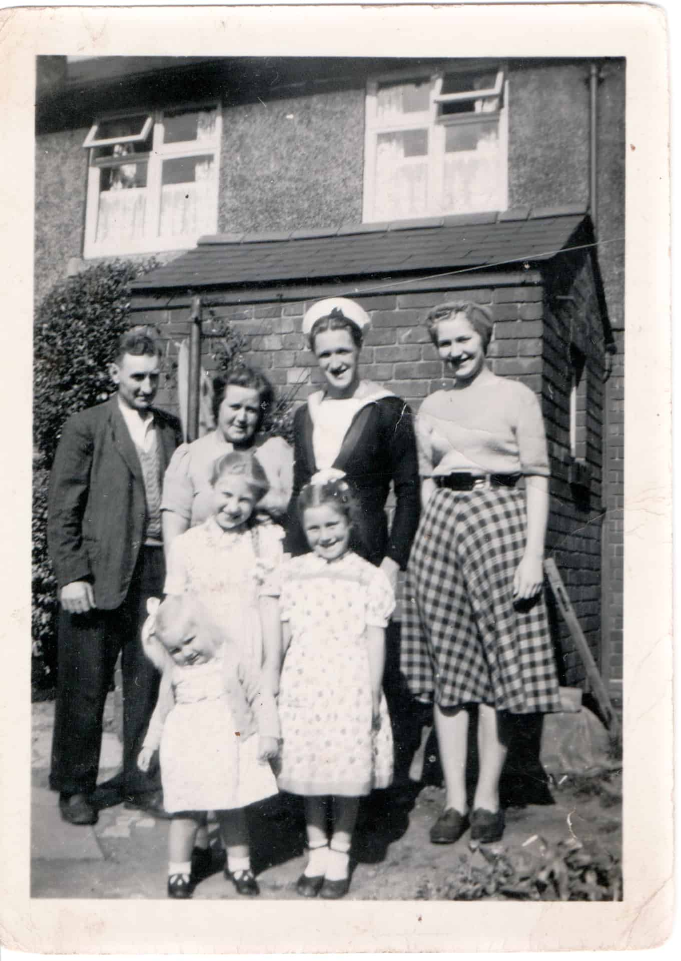 John Henry Price (back row in sailor's uniform) and his family photographed outside their house in Warley Road, Oldbury, in 1950.