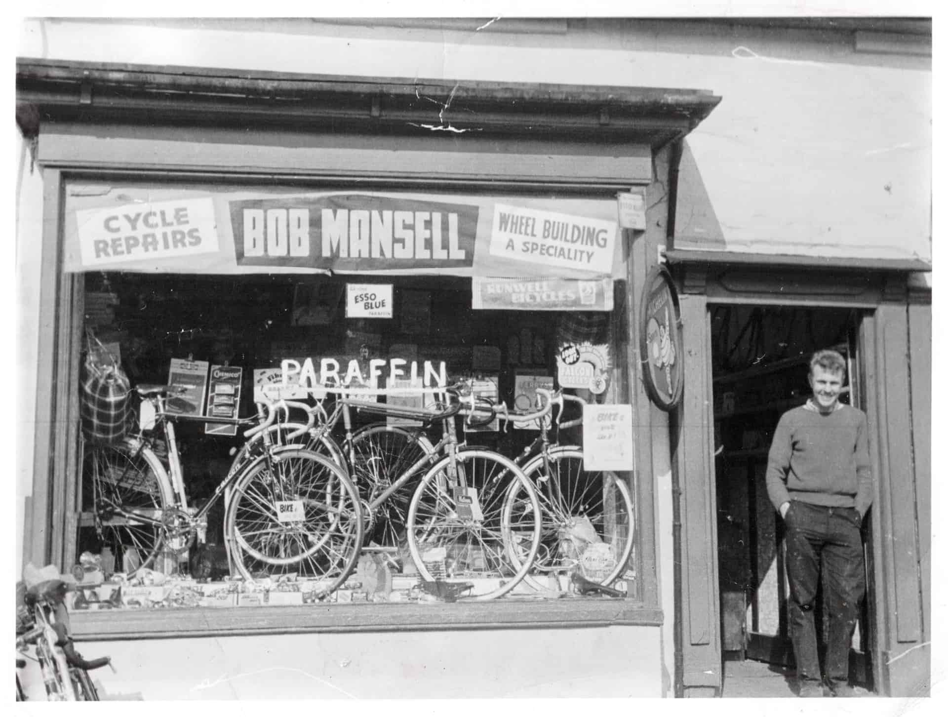 "Bob Mansell Cycles 504 Oldbury Road, Smethwick, Staffs. Bob's daughter Juanita remembers ""Falcon bikes, probably Brookes saddle in the window. Grandad and dad used to sell Esso Blue parafin out of the back of the Morris Traveller. The floor boards were bare and there was a cellar with an opening at the front of the shop. Dad was always repairing wheels in the back, I remember the big tin tubs of lube and ball bearings rolling around, they were so little."""