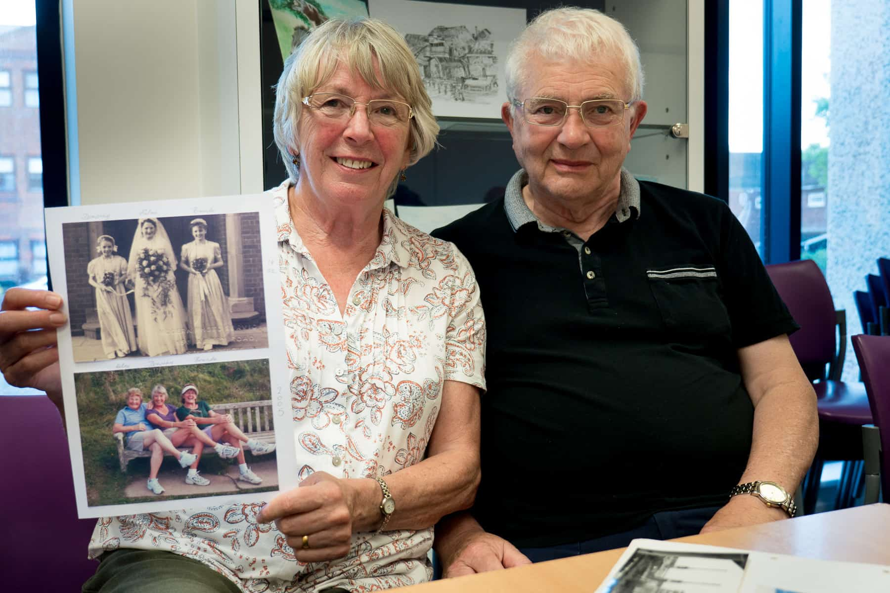 Gary and Dorothy photographed in May 2018. Dorothy is holding two photos placed together. The top photo shows the wedding her of sister Edna in 1952 at St Hilda's Church, Oldbury with herself and other sister Brenda as bridesmaids. The bottom photograph show the three sisters taken together in 2014.