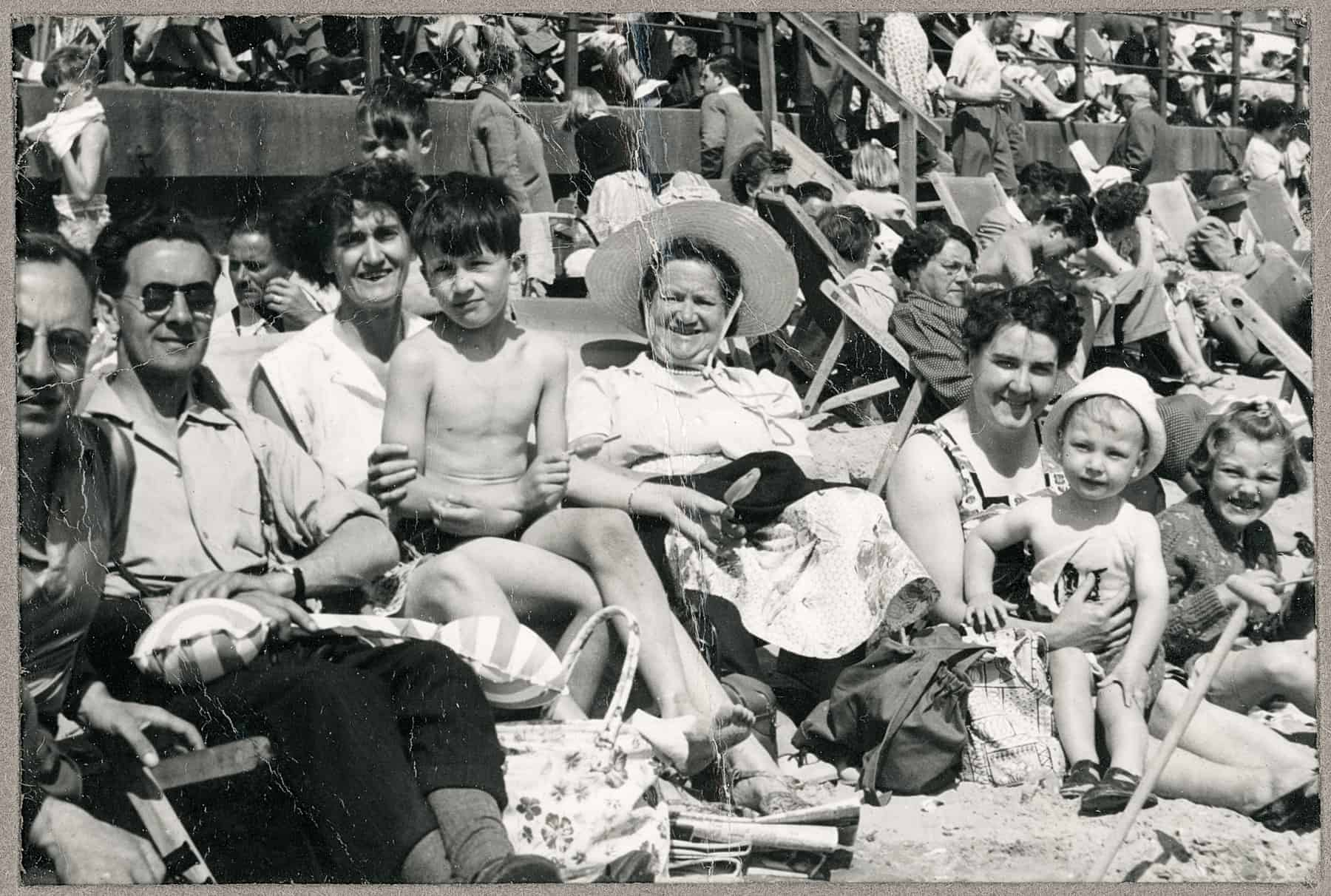 This photo was taken on holiday in Weymouth, 1950s. It's very crowded isn't it? That's practically the whole family. That's my Dad on the far left, and there is me as a boy in the arms of my mum.