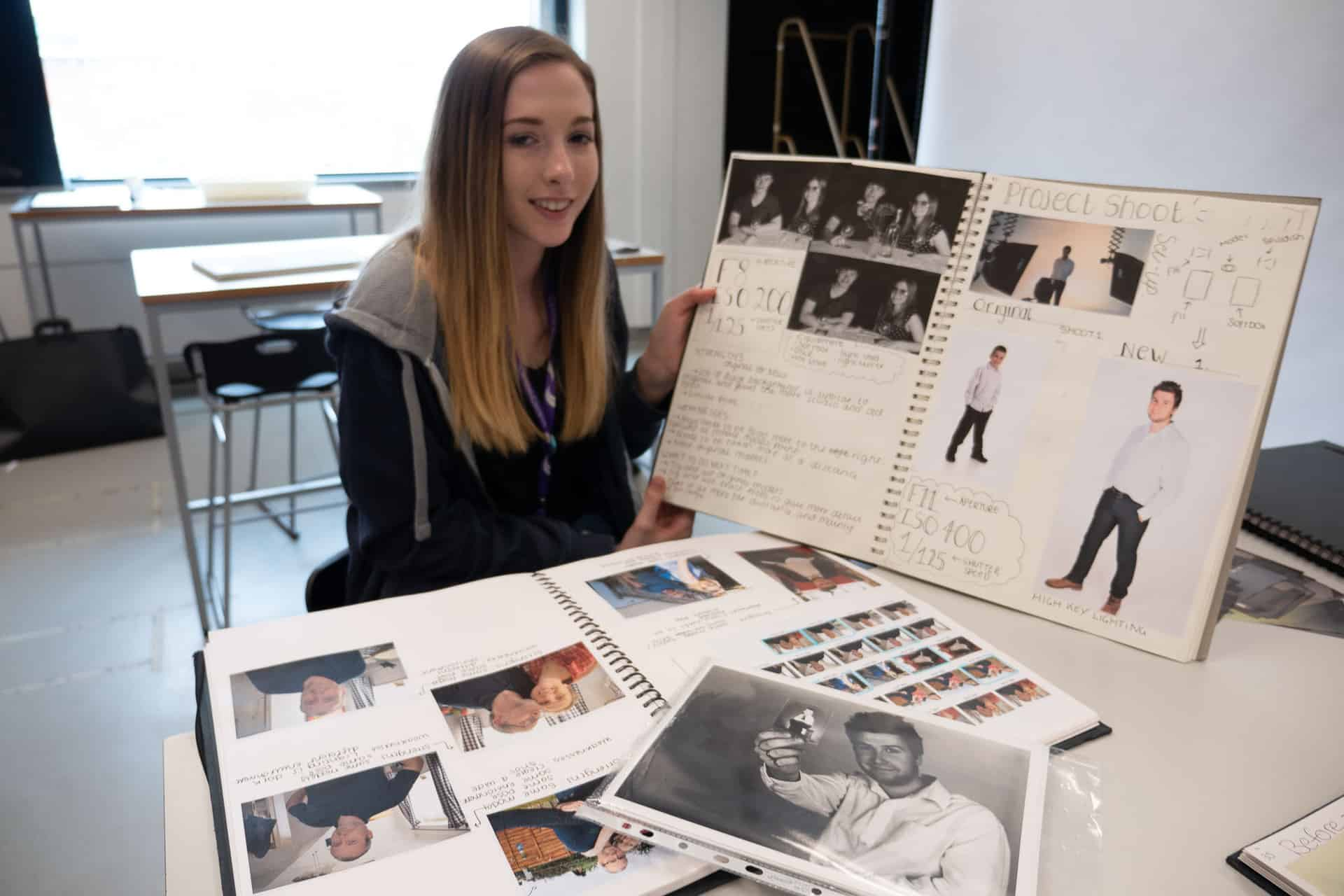 A student at Sandwell College shows off her project book featuring work made with her family collection as part of the Living Memory project