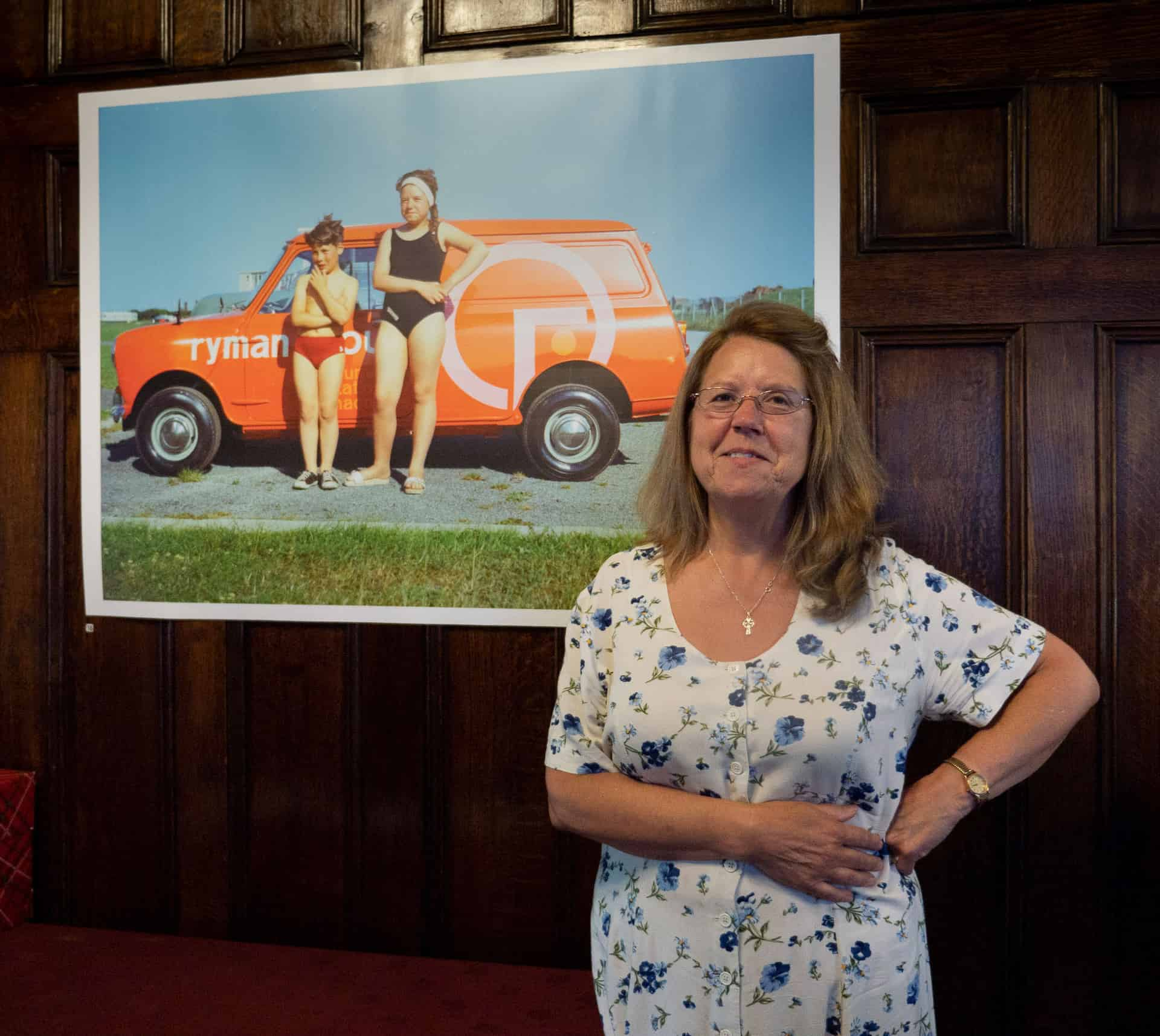 Cheryl Aston (nee Moss) stands in front of a photograph of herself taken by her father Ron Moss in 1967