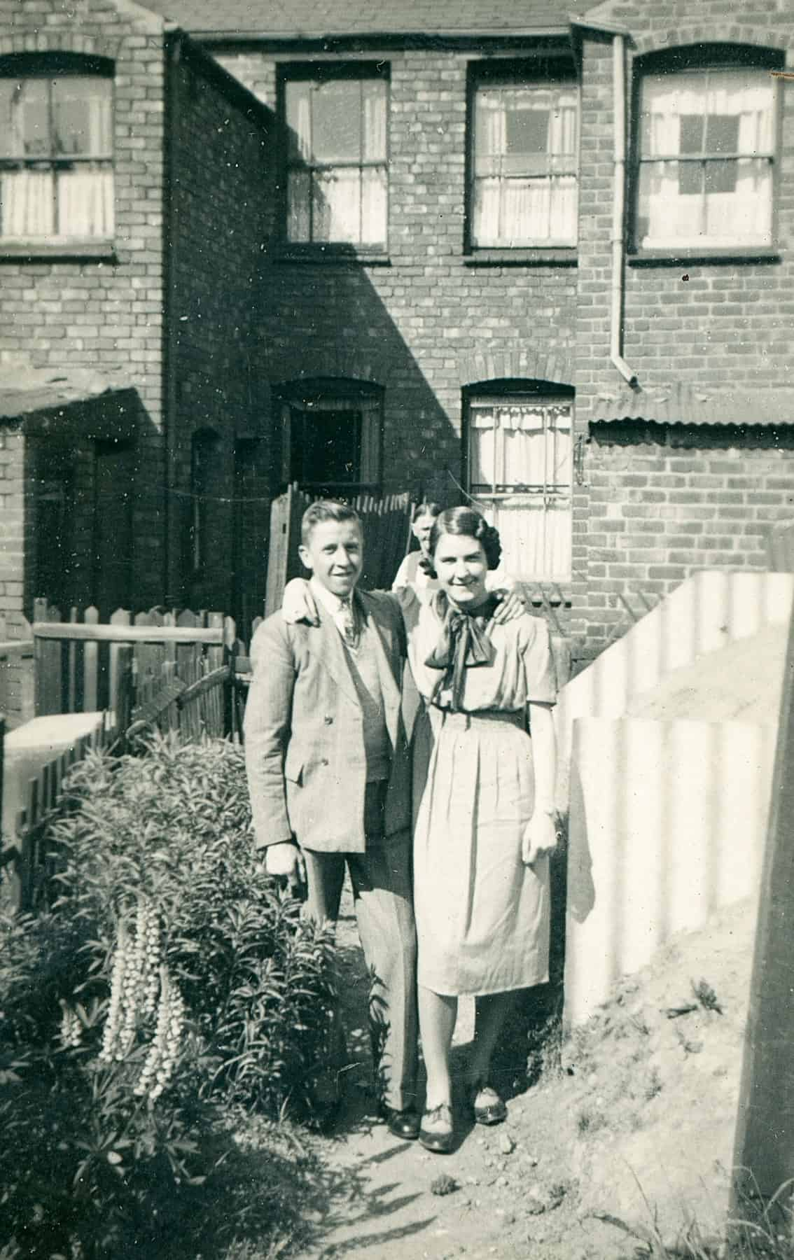 That's my mum and that's her brother Frank. This is taken in the back garden of that road that my grandparents lived in and that's the Anderson shelter. You can see they used to have lupins in the garden and rhubarb.