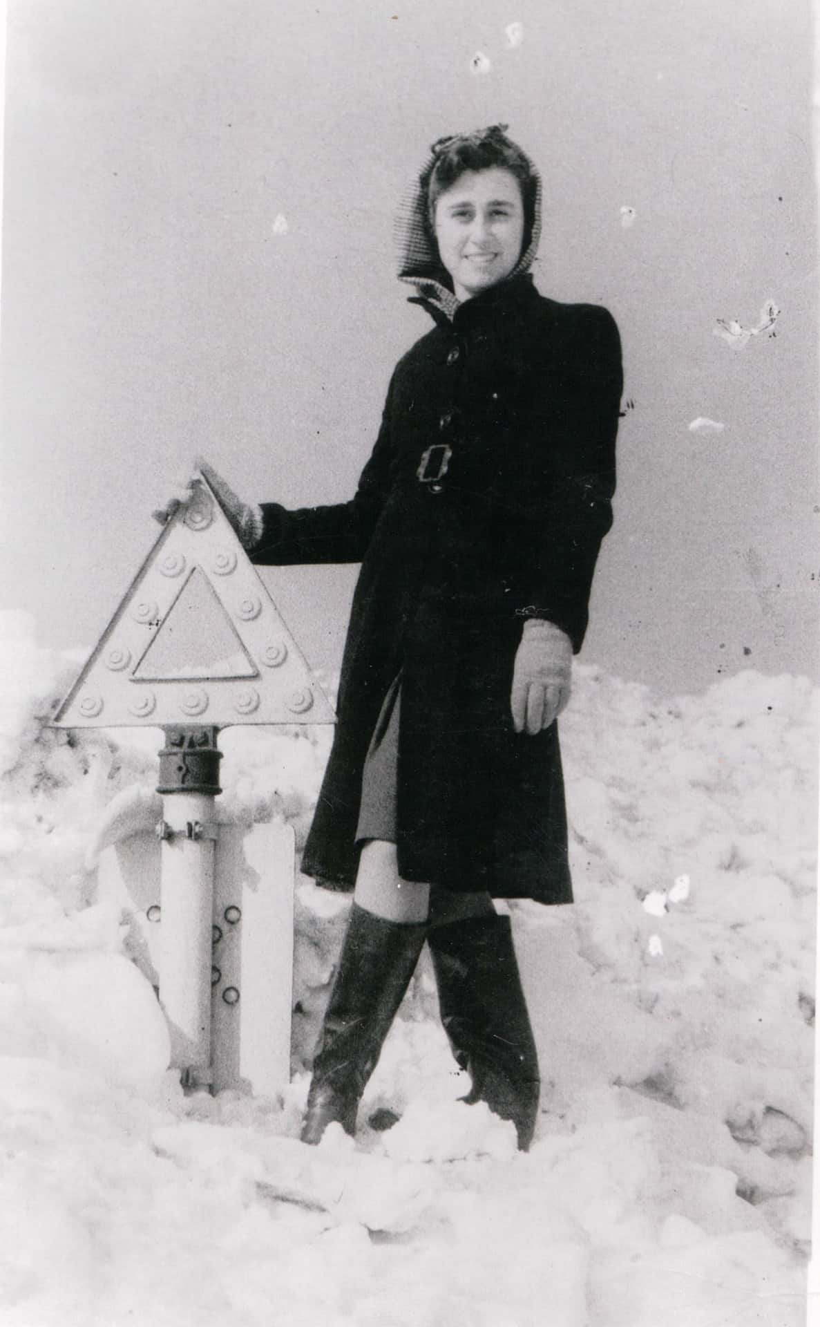 Mary Waters standing on a snow drift on the Birmingham New Road in 1947.