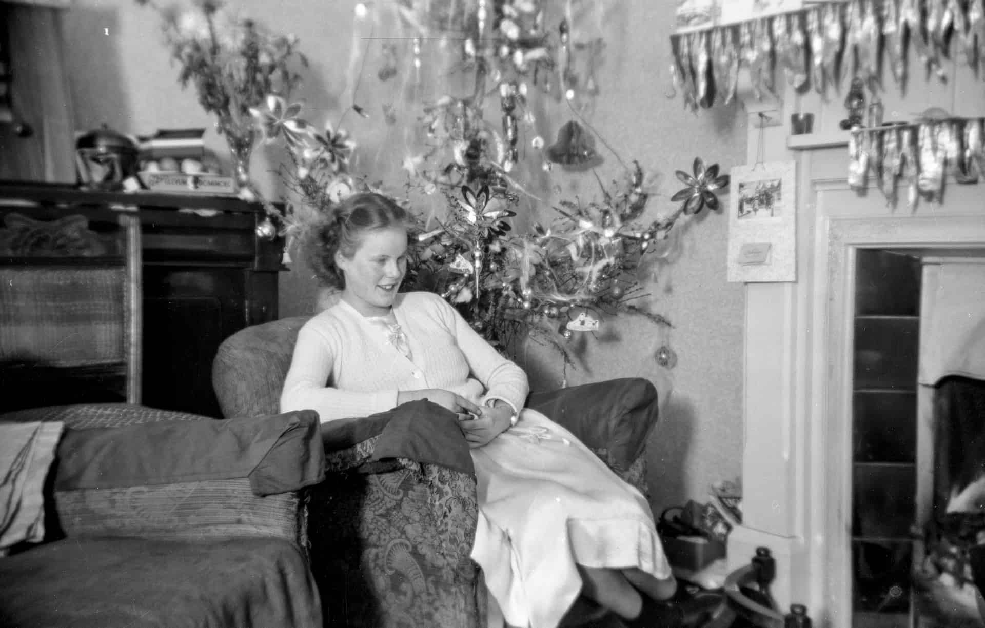 This is my sister at Christmas. You can see the austerity of the Christmas tree!There's the old radio set, because there was no television then, just a radio. Most of the decorations on the tree are home made.