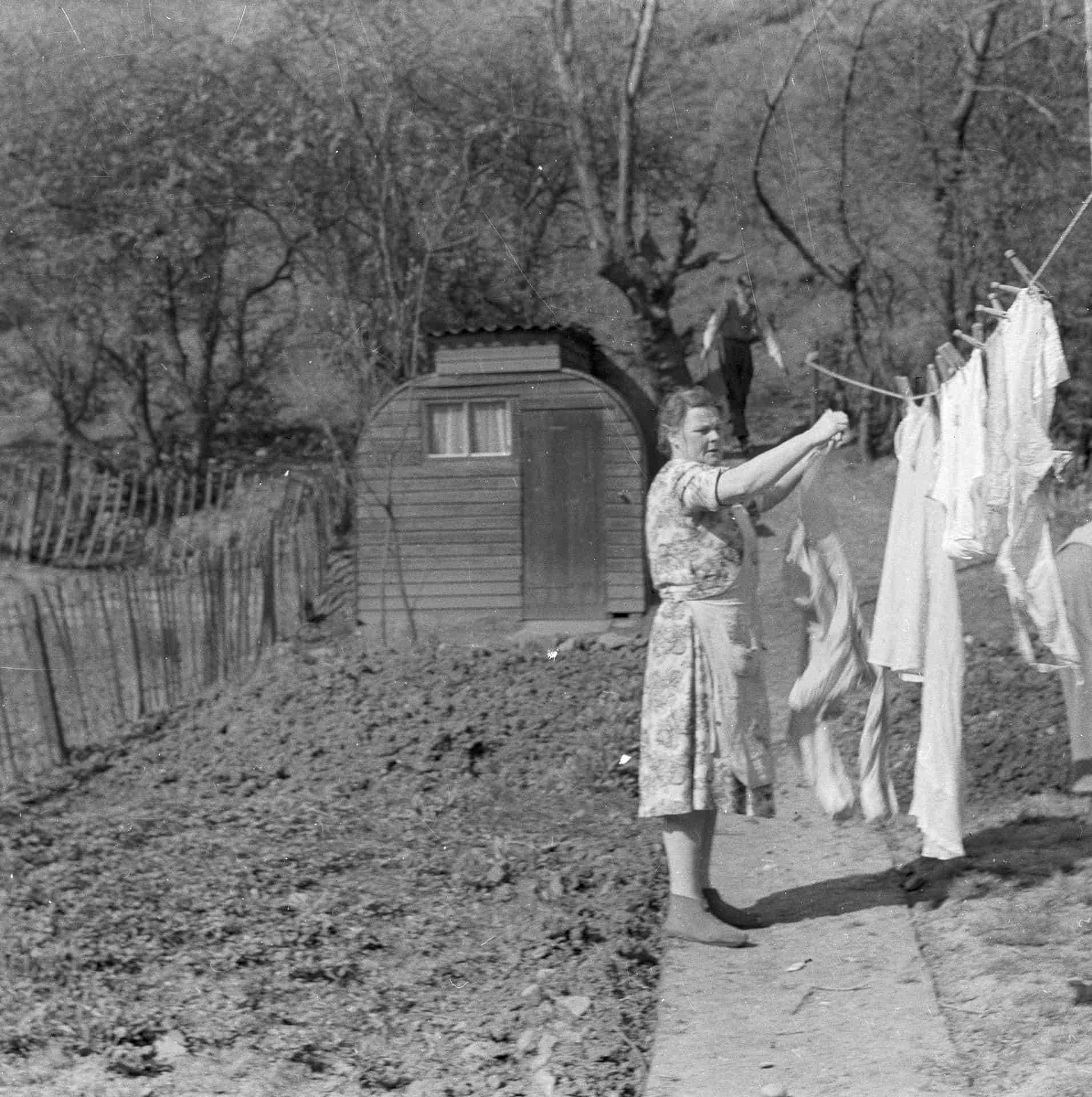 This is of my mum pegging out the washing. In the background there is a shed made up after the war from the old Anderson air raid shelter. The Anderson air raid shelter was narrower than that, it's been extended a bit and dad made it into a shed, he used to keep the bikes and the motorbikes and various odds and ends.