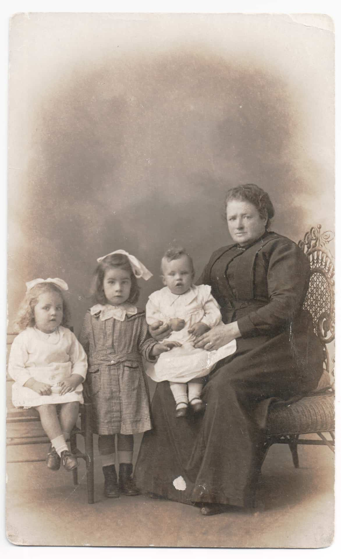 This is a studio photo of my mom who is in the middle, with her granny. We knew her as Granny Sadler. My mom, is probably about 4, so it's taken in 1918 in Dundee. The other children are her cousins. Her grandmother brought her  up as her parents had died by then.
