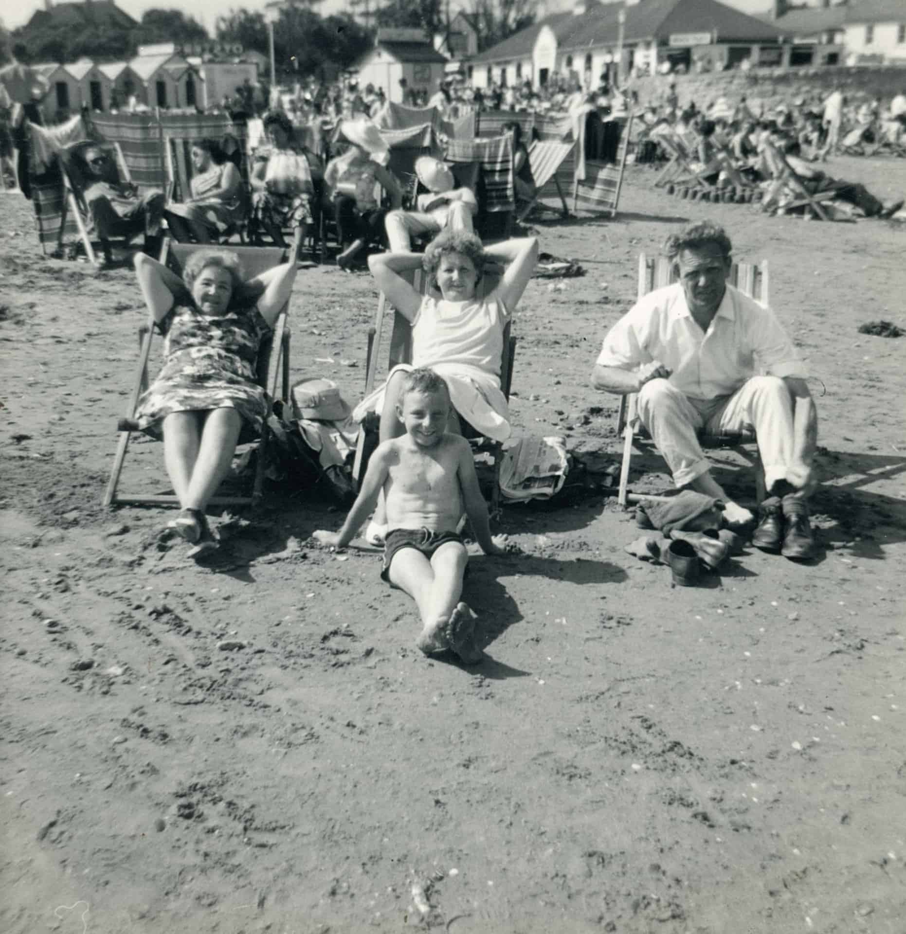 Nan, Mom and Dad in deckchairs and my mate Derek in the foreground on the beach in the 1960s