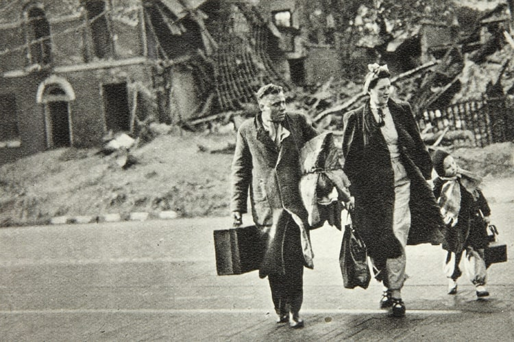 Bombed out family cross the road with their belongings. Photograph from the Ministry of Information. 1941